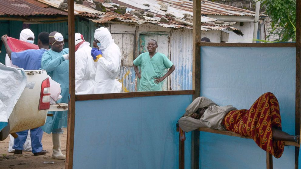 Medical workers of the John Fitzgerald Kennedy hospital in Monrovia, responsible for transport of the bodies of Ebola virus victims, wear their protective suits as they walk past a sick woman waiting for assistance, on Sept. 6, 2014.