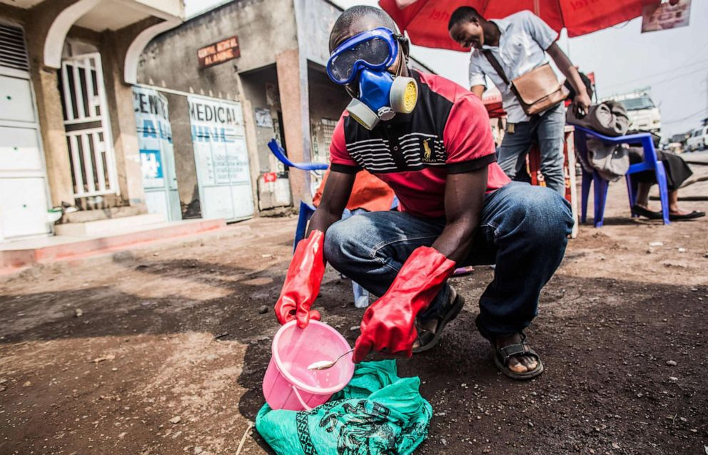 PHOTO: A health worker wears protective gear and mixes water and chlorine in Goma on July 31, 2019.