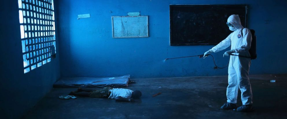 PHOTO: A Liberian health worker disinfects a corpse after the man died in a classroom now used as Ebola isolation ward on Aug. 15, 2014 in Monrovia, Liberia.