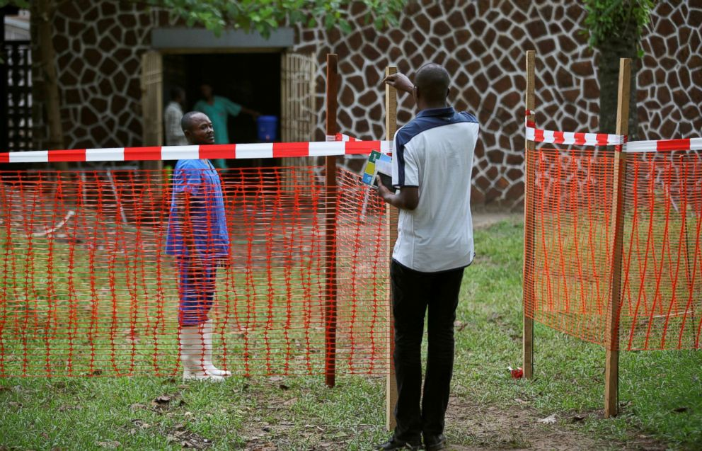 PHOTO: A resident speaks to a medical worker through a cordon ribbon, near the isolation facility prepared to receive suspected Ebola cases, at the Mbandaka General Hospital, in Mbandaka, Democratic Republic of Congo, May 20, 2018.