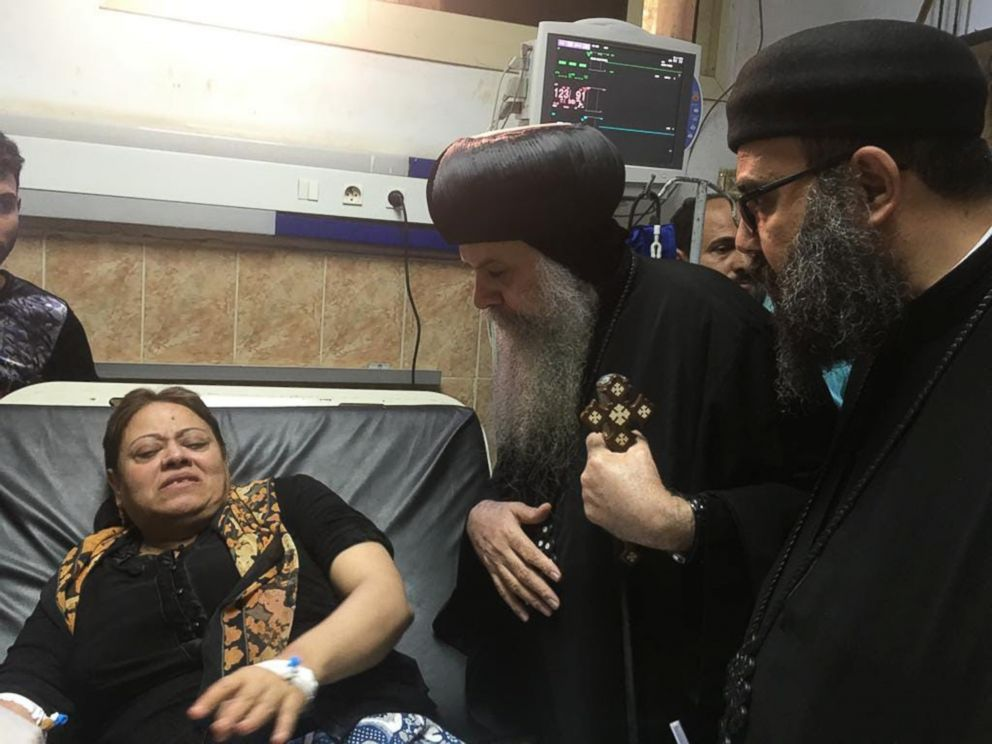 PHOTO: Egypts Coptic priest Agathon speaks to a woman who was wounded when gunmen attacked a bus carrying Coptic Christians, at the Sheikh Fadel hospital in Beni Mazar on November 2, 2018.