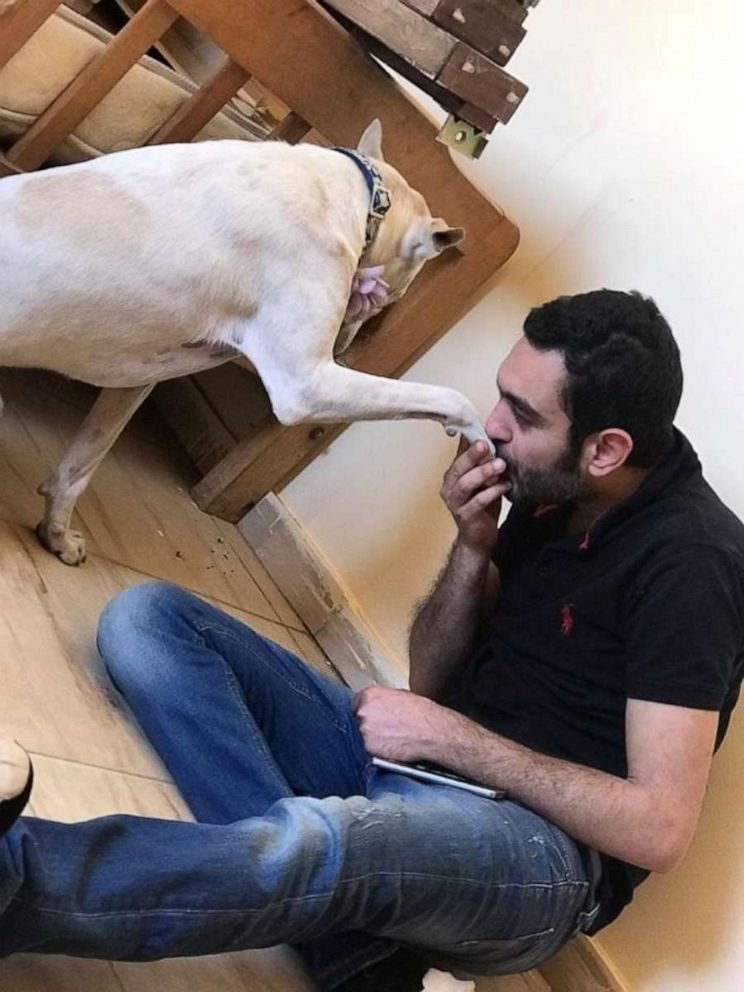 PHOTO: Ahmed Al Shurbaji kisses the hand of one of the baladi dogs at HOPE shelter, in Cairo.