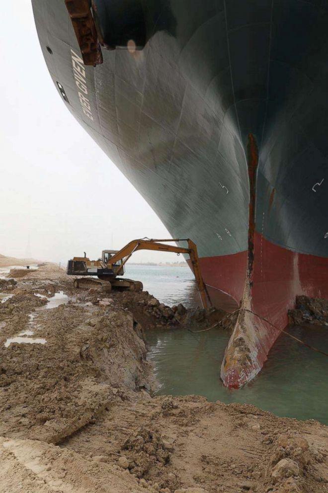 الصورة: حفارة تحاول تحرير سفينة حاويات عالقة إيفر جيفن ، إحدى أكبر سفن الحاويات في العالم ، بعد أن جنحت في قناة السويس ، مصر في 25 مارس 2021.