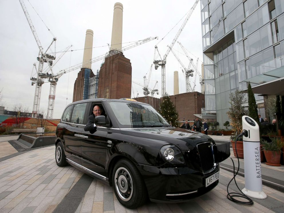 PHOTO: CEO of London EV Company, Chris Gubbey poses inside the new electric TX eCity taxi connected to a sample electric vehicle charger at the Battersea power station in London, Dec. 5, 2017.