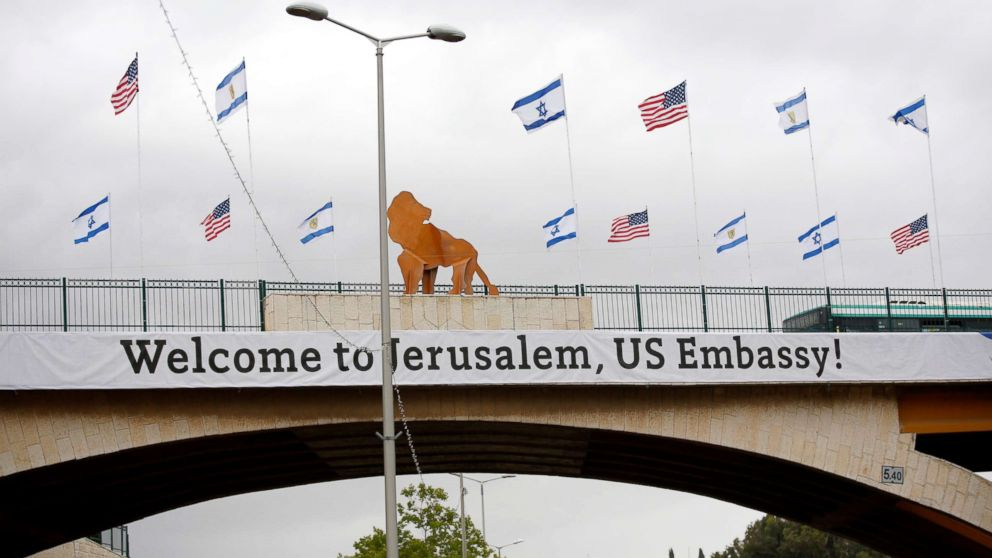 A sign and flags appear on a bridge nearby the US consulate that will act as the new US embassy in the Jewish neighborhood of Arnona, May 13, 2018.