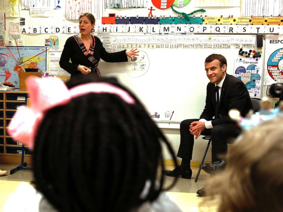 PHOTO: French President Emmanuel Macron listens to teacher Caroline Loret as he visits the Emelie pre-school in Paris, March 27, 2018.