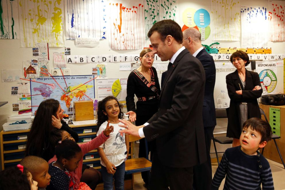 PHOTO: French President Emmanuel Macron speaks to pre-school children as he visits the Emelie pre-school in Paris, March 27, 2018.