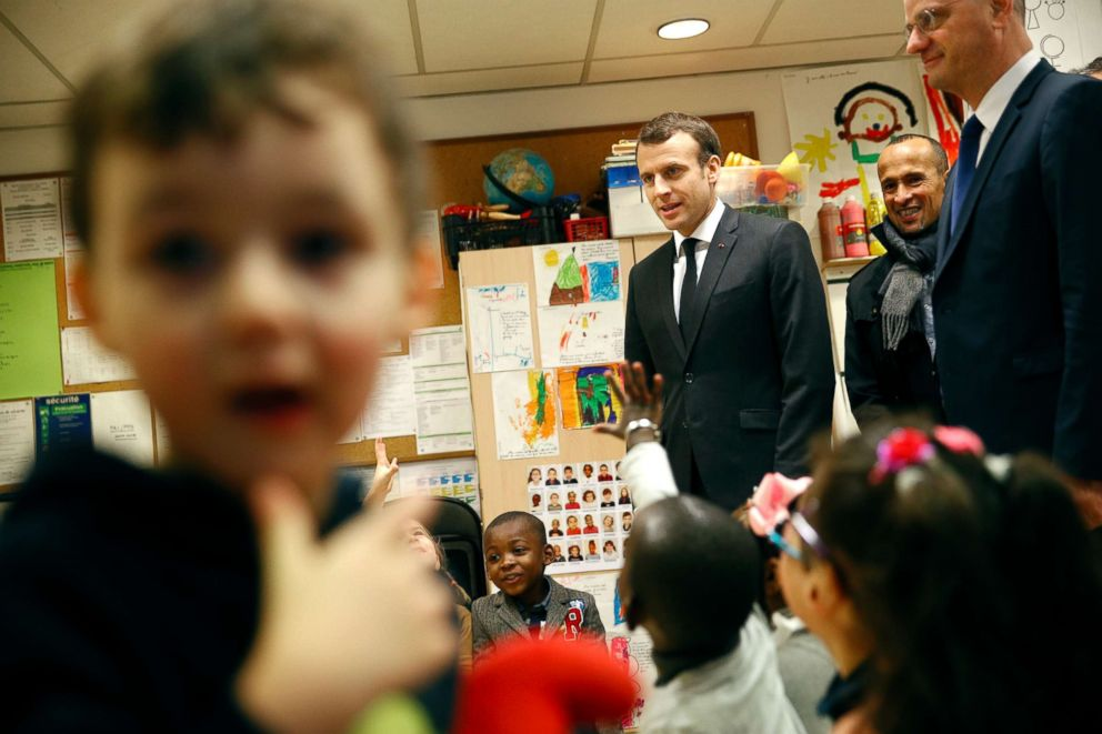 PHOTO: French President Emmanuel Macronand French Education Minister Jean-Michel Blanquer speak to preschool children as they visit the Emelie pre-school in Paris, March 27, 2018.