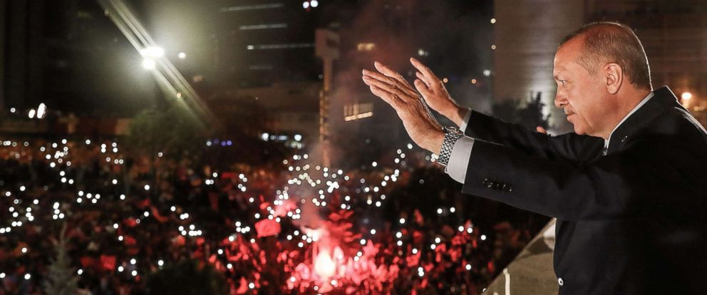 PHOTO: Turkish President Tayyip Erdogan waves to supporters gathered above a balcony at the headquarters of the AK Party in Ankara, June 24, 2018, as they celebrate Erdogan winning five more years in office.