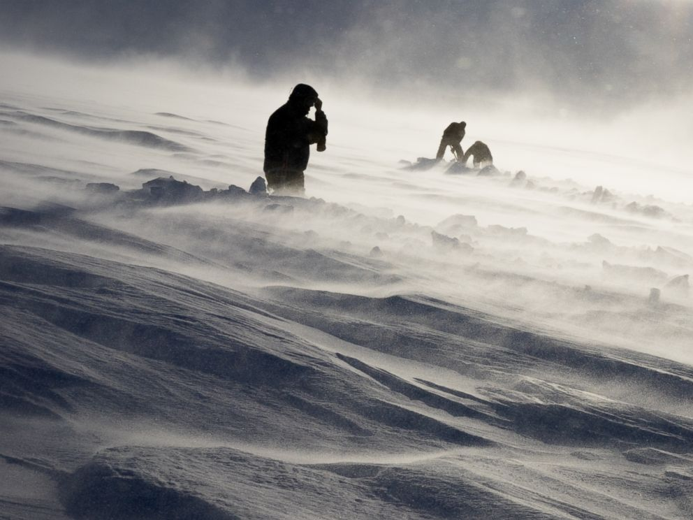 PHOTO: Dr. Graham Hill, Dr. John Stodt and helicopter pilot Harlan Blake dig out a buried measurement site on a glacier on Mount Terror during a windstorm, Jan. 12, 2016.