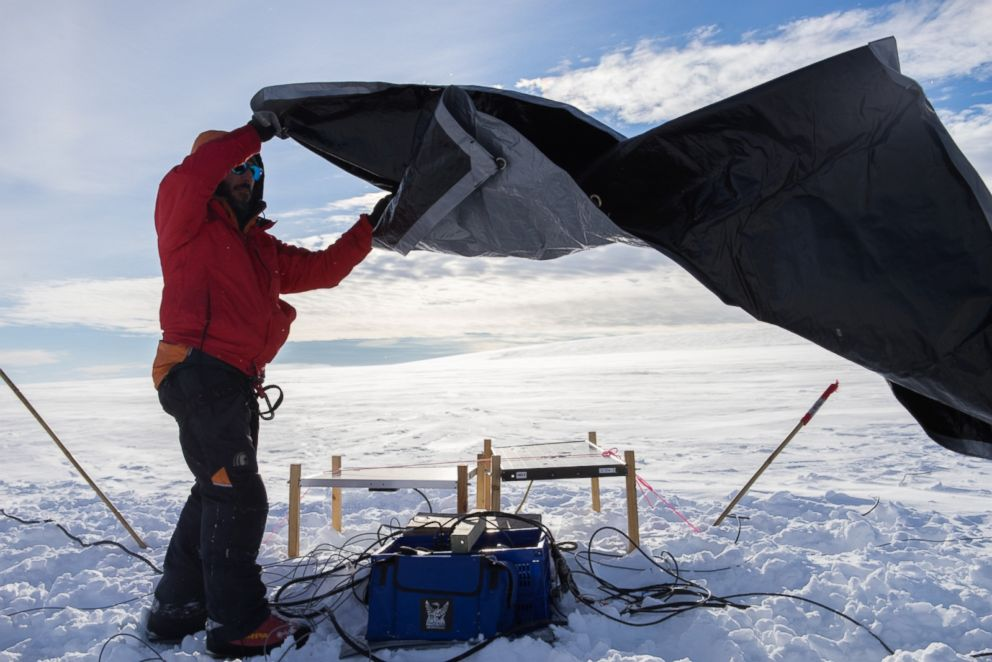 PHOTO: Dr. Paul Bedrosian covers the geophysics equipment before leaving it on a glacier to collect data.