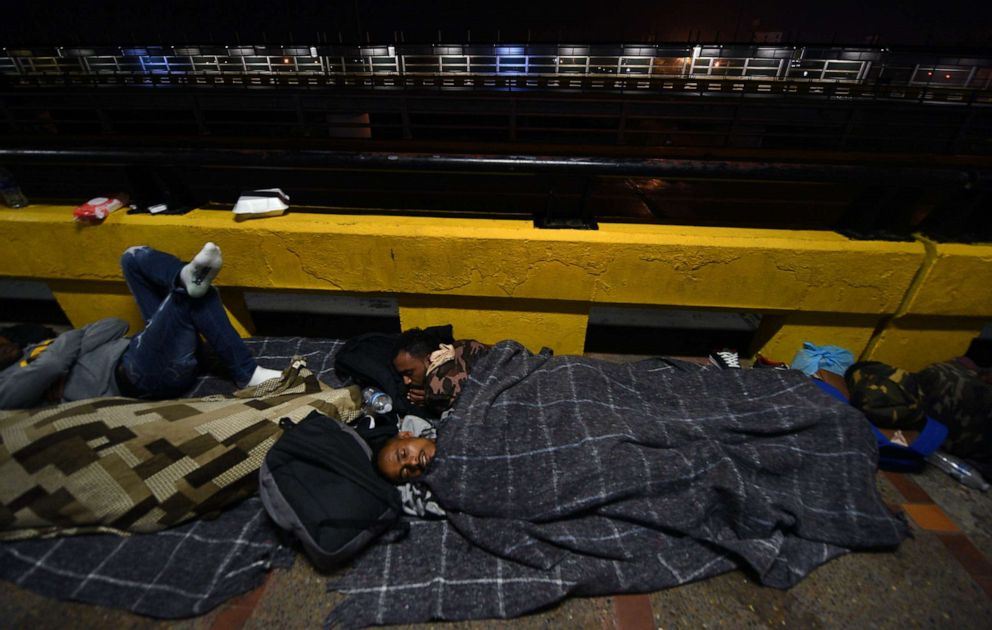 PHOTO: Immigrants from Eritrea wait on bridge in Matamoros, Mexico near the U.S. border, July 2, 2018. They spent 3 months on the journey through Brazil to reach the U.S. where they were eventually allowed in to be processed for credible fear.