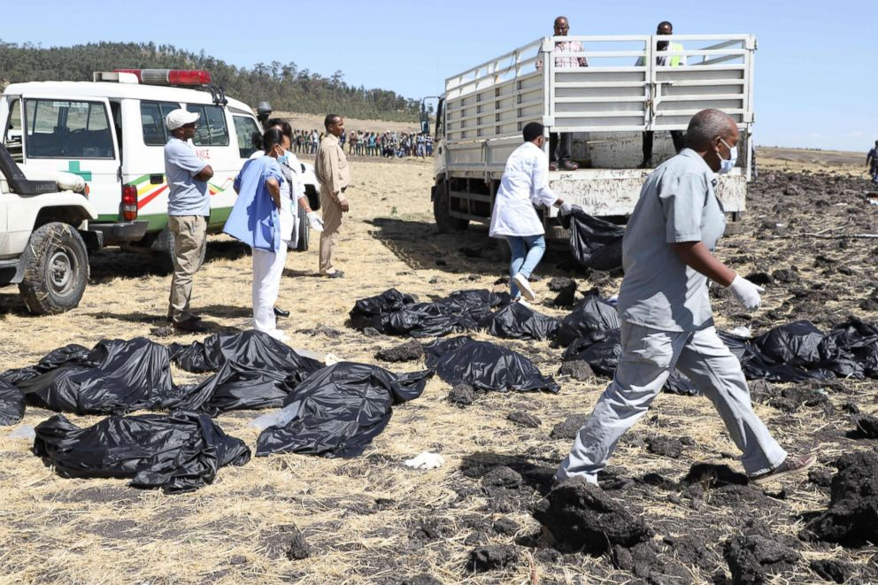Rescue teams walk past collected bodies in bags at the crash site of Ethiopia Airlines near Bishoftu, southeast of Addis Ababa, Ethiopia, March 10, 2019.
