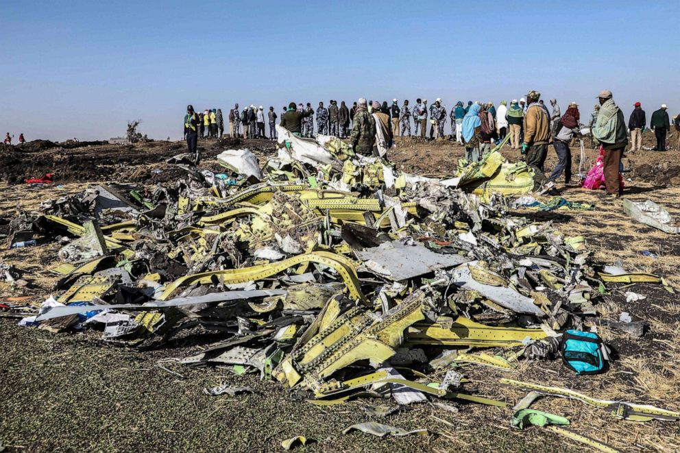 People stand near collected debris at the crash site of Ethiopia Airlines near Bishoftu, southeast of Addis Ababa, Ethiopia, March 11, 2019.