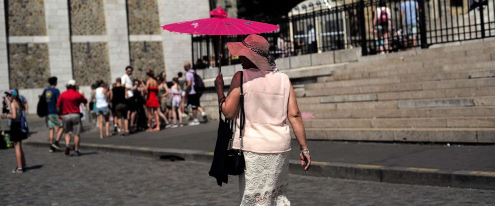 PHOTO: A tourist shelters under an umbrella Wednesday, June 26, 2019, in the Montmartre district of Paris.