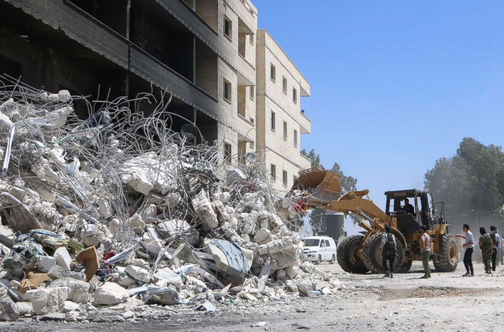 PHOTO: A tractor clears the rubble of destroyed buildings, Aug. 13, 2018, following an explosion at an arms depot in a residential area in Syrias northern Idlib province city of Sarmada in which dozens of people were reportedly killed.
