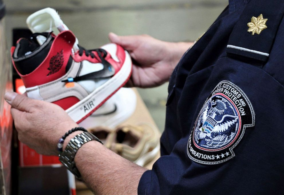 PHOTO: This undated photo provided by U.S. Customs and Border Protection shows an agent holding one of more than 14,800 pair of counterfeit Nike shoes, seized in a shipment arriving from China at the Los Angeles-Long Beach sports complex.