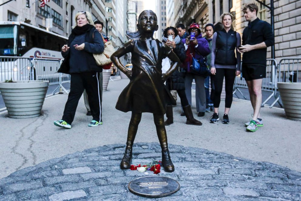 PHOTO: Tourists take photos of The Fearless Girl statue as it stands across from the Wall Streets famous Charging Bull to draw attention to the gender equality and lack of female managers, March 9, 2017, in New York.