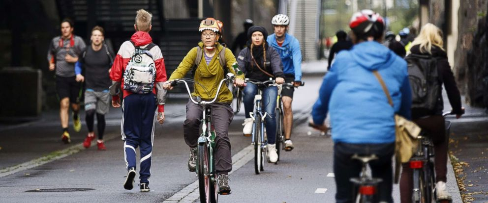 """PHOTO: Cyclists and pedestrians pass the """"Baana"""" road that was built on former train tracks and is now reserved for pedestrians and bicycles in Helsinki, Finland, Sept. 18, 2015."""