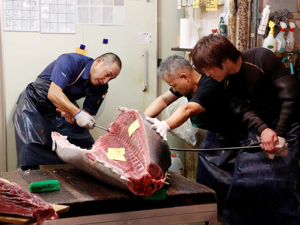 PHOTO: Wholesalers cut fresh tuna fish at the Tsukiji fish market in Tokyo, Sept. 25, 2018.