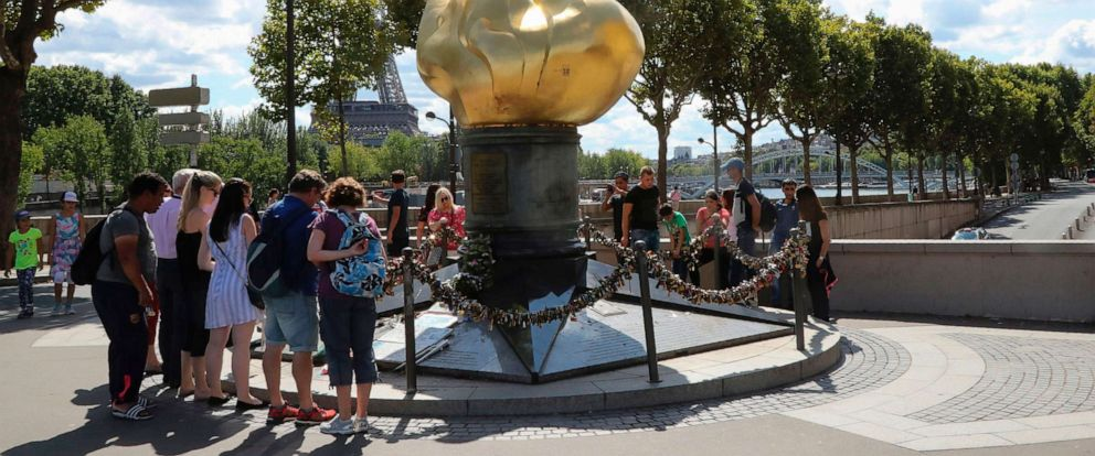 """PHOTO: People walk around the """"Liberty Flame"""" where fans memorialized Princess Diana after her death in Paris, Aug. 31, 2017."""
