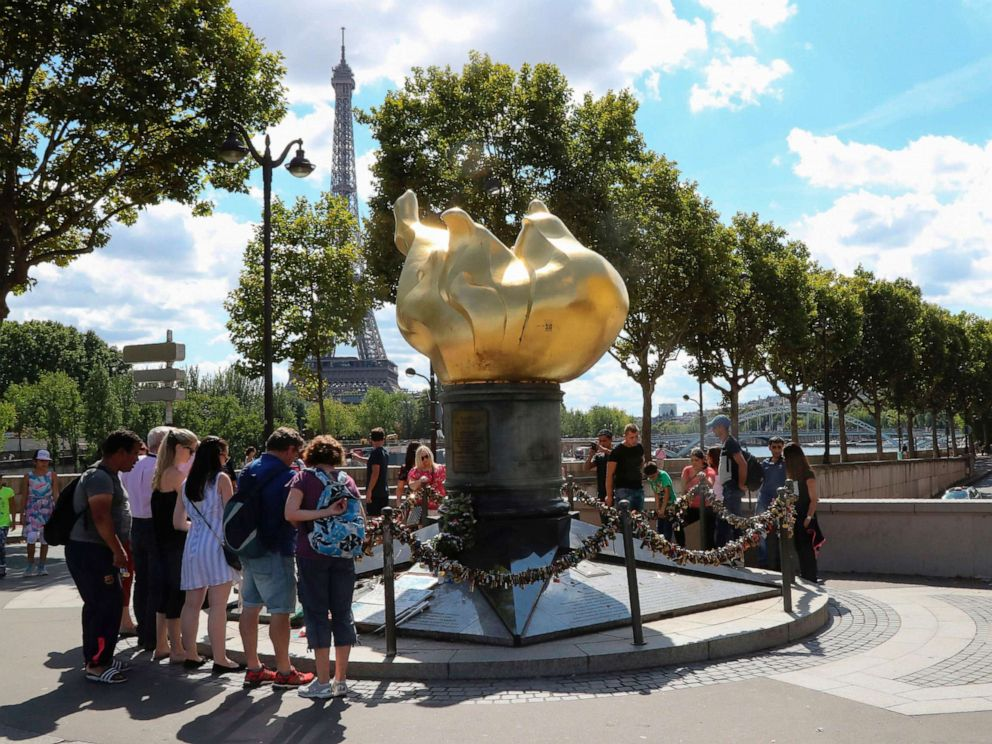 PHOTO: People walk around the Liberty Flame where fans memorialized Princess Diana after her death in Paris, Aug. 31, 2017.