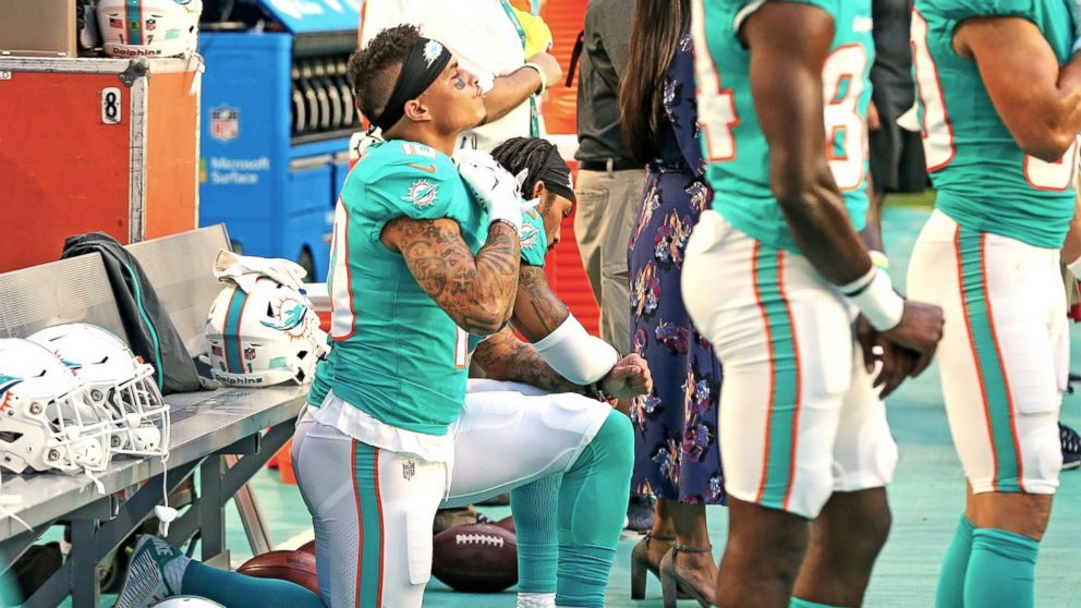 Miami Dolphins receivers Kenny Stills and Albert Wilson kneel during the national anthem as they prepare to play the Tampa Bay Buccaneers at Hard Rock Stadium in Miami Gardens, Fla., Aug. 9, 2018.