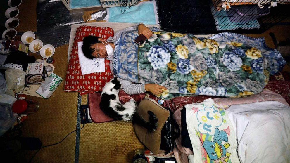 FOTO: Sakae Kato yace en la cama junto a Charm, un gato que rescató hace cinco años y que está infectado con el virus de la leucemia felina, en su casa en una zona restringida en Namie, prefectura de Fukushima, Japón, el 20 de febrero de 2021.