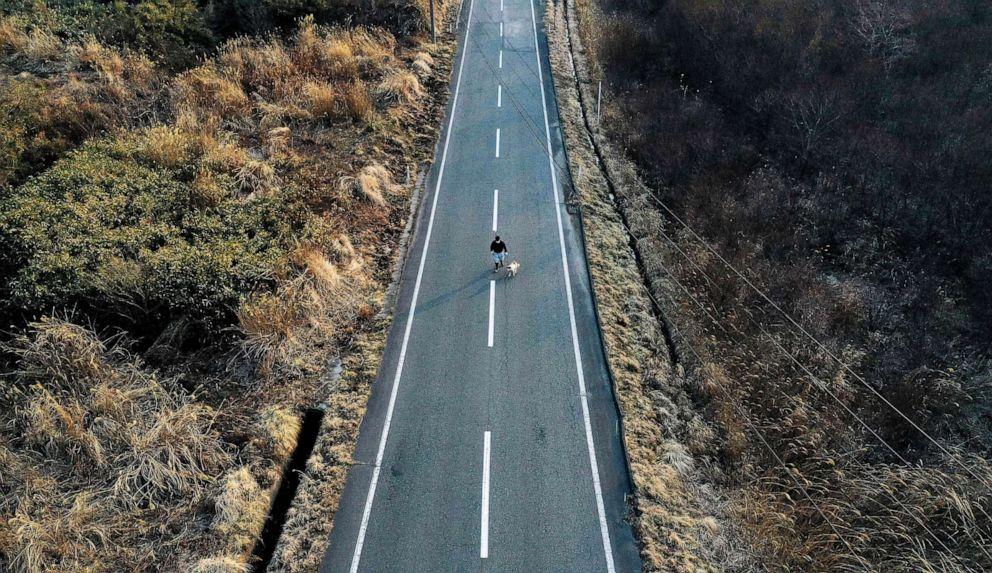 FOTO: Una vista aérea muestra a Sakae Kato paseando a Pochi, su perro que rescató hace cuatro años, en una carretera vacía entre zonas restringidas en Namie, Prefectura de Fukushima, Japón, el 20 de febrero de 2021.