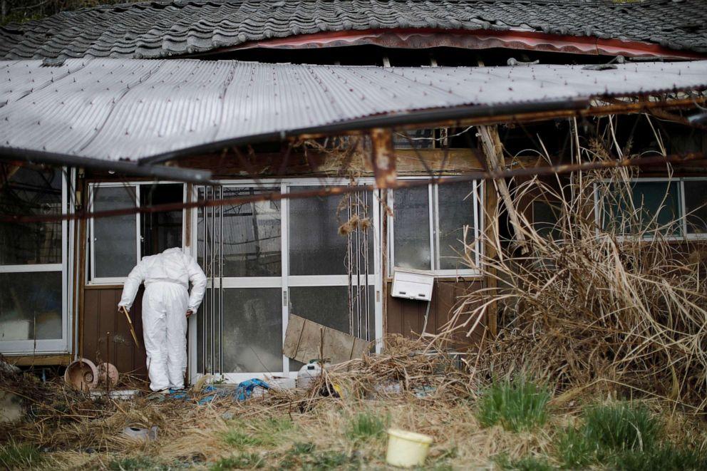 FOTO: Hisae Unuma mira dentro de su casa en la que vivía antes de ser evacuada en Futaba, Prefectura de Fukushima, Japón, el 23 de febrero de 2021.