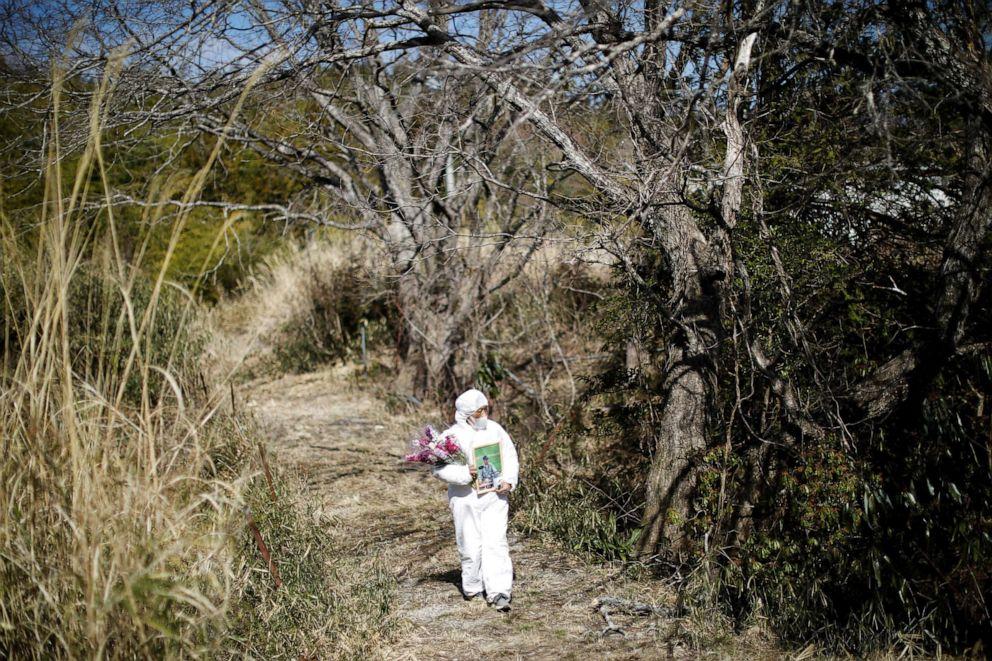Hisae Unuma se dirige al cementerio de su familia cerca de su casa en la que vivía antes de ser evacuada mientras visita la casa en el aniversario del fallecimiento de su esposo en una zona restringida en Futaba, prefectura de Fukushima, Japón, el 23 de febrero de 2021.