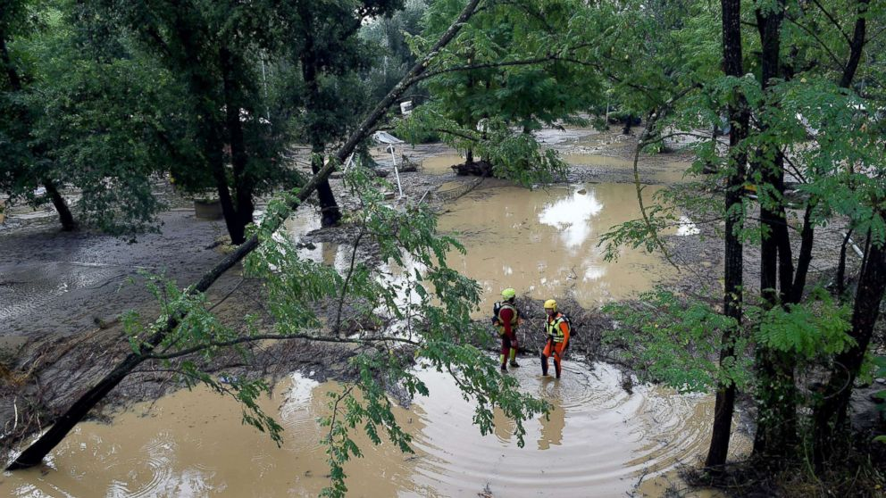 Rescuers stand in a flooded area of a camping as storms and heavy rains sweep across France, Aug. 9, 2018, in Saint-Julien-de-Peyrolas, southern France.