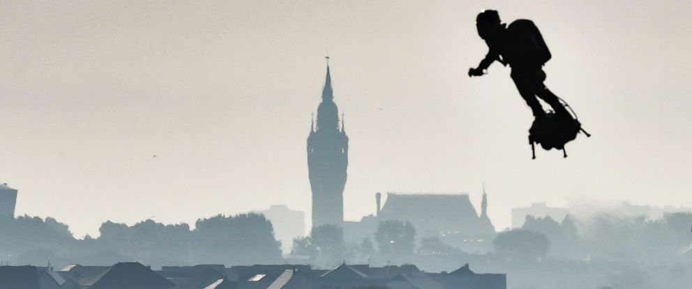 "PHOTO: Franky Zapata on his jet-powered ""flyboard"" flies past the belfry of the city hall of Calais after he took off from Sangatte, northern France, on Aug. 4, 2019, during his attempt to fly across the 22-mile English Channel crossing in 20 minutes."