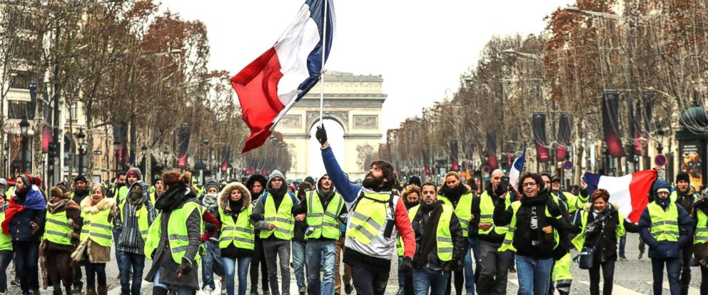 PHOTO: A protester wearing a yellow vest (gilet jaune) waves the French national flag during a demonstration against rising costs of living blamed on high taxes on the Champs-Elysees in Paris, on Dec. 15, 2018.