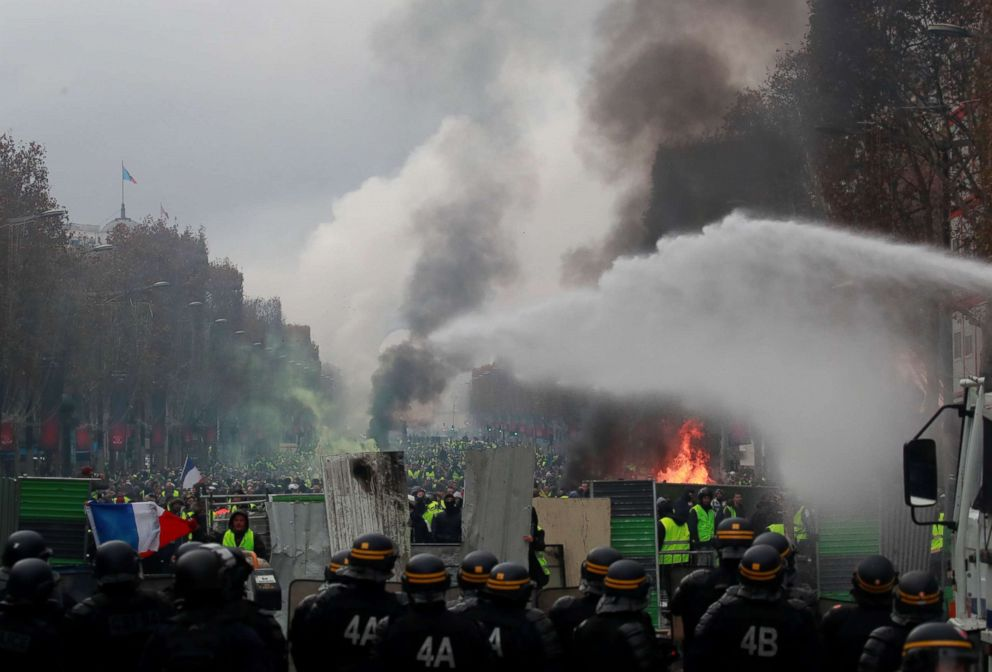 PHOTO: Protesters wearing yellow vests, a symbol of a French drivers protest against higher fuel prices, run from police during riots on the Champs-Elysees in Paris, Nov. 24, 2018.