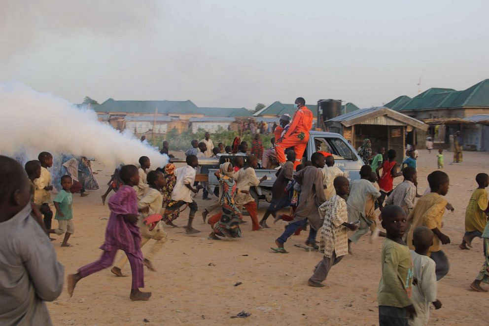 Children playfully run away from a fumigation machine mounted on the back of a pick-up used in a displaced camp in Maiduguri in northeast Nigeria's Borno state on April 15, 2020, as the Borno State Environment Protection Agency proceeds to disinfect the camps as a preventive measure against the spread of the novel coronavirus.Audu Marte/AFP via Getty Images