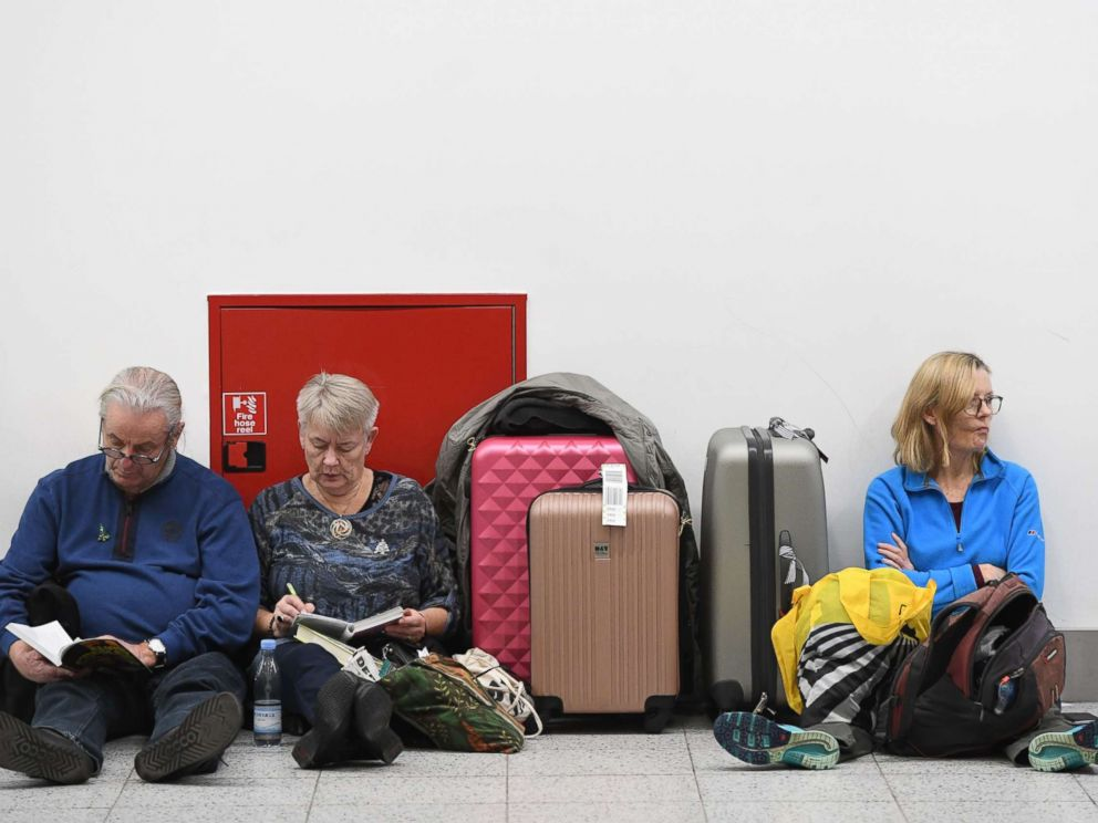 PHOTO: Passengers rest with their luggage at the Gatwick airport in Sussex, southeast, England, Dec. 21, 2018.