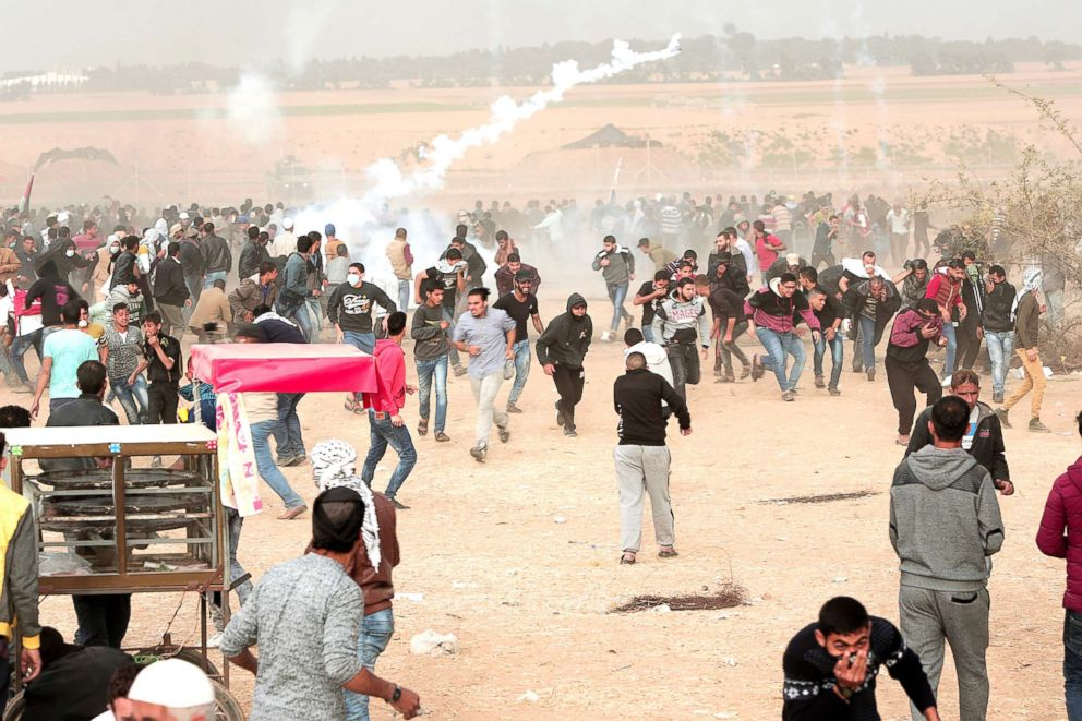 PHOTO: Palestinian protesters run for cover from teargas during clashes with Israeli troops along Gazas border with Israel, east of Khan Younis, Gaza Strip, April 20, 2018.