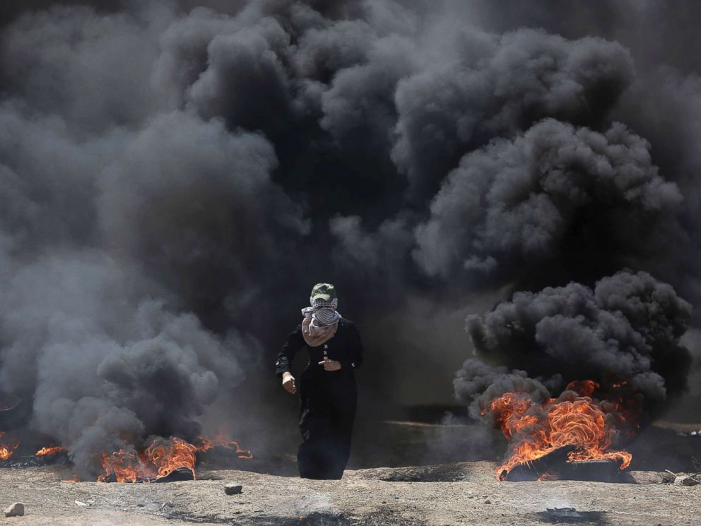 PHOTO: A Palestinian woman walks through black smoke from burning tires during a protest on the Gaza Strips border with Israel, May 14, 2018.