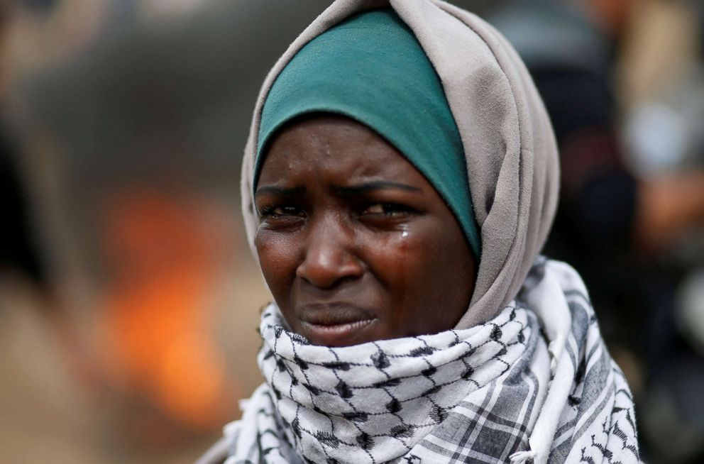 A woman demonstrator reacts to tear gas fired by Israeli troops during clashes at a protest at the Israel-Gaza border where Palestinians demand the right to return to their homeland, east of Gaza City, April 20, 2018.
