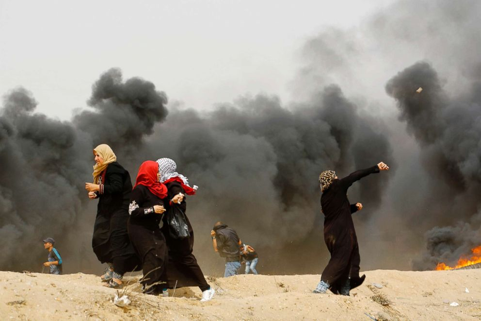 PHOTO: Palestinian women throw stones past smoke plume rising from burning tires during clashes with Israeli forces across the border on April 20, 2018 at the Gaza Strips border with Israel.