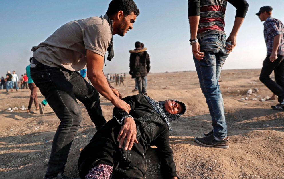 PHOTO: A Palestinian youth tends to a fallen woman affected by tear gas during clashes with Israeli forces east of Gaza City on May 15, 2018.