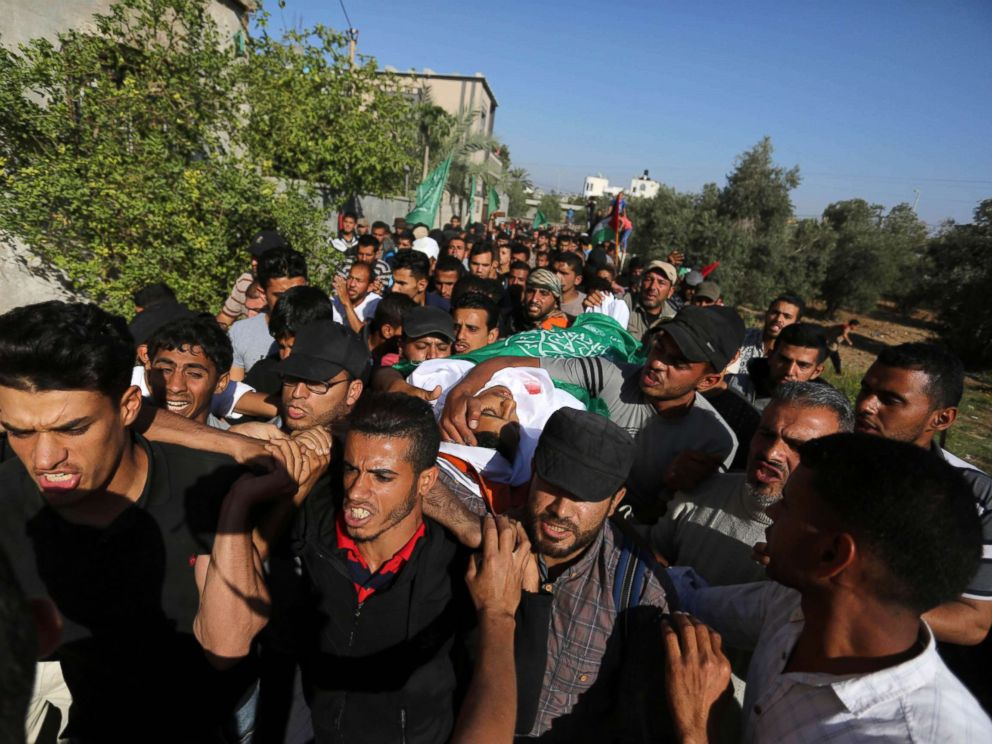 Mourners carry the body of Palestinian Mahmoud Abu Taima, who was killed by Israeli troops during clashes in a tent city protest where Palestinians demanded the right to return to their homeland, May 14, 2018, in the Gaza Strip.