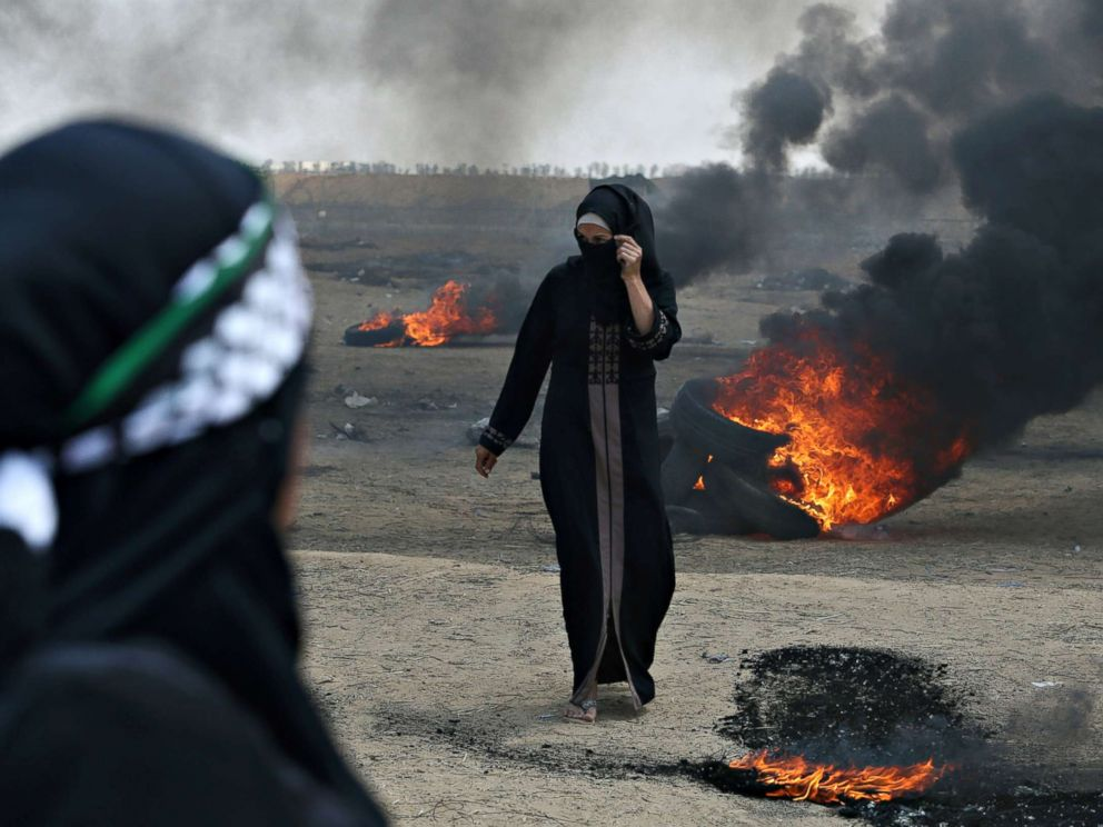 PHOTO: A Palestinian demonstrator walks past burning tires during a protest against the U.S. embassy move to Jerusalem at the Israel-Gaza border in the southern Gaza Strip on May 14, 2018.