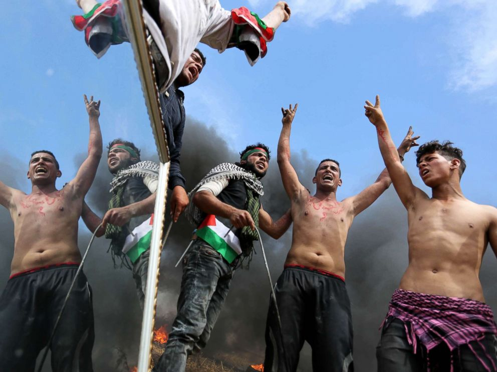 PHOTO: Palestinian protesters use a reflective mirror to divert the attention of members of the Israeli forces during a tent city protest at the Israel-Gaza border, in Khan Yunis in the southern Gaza Strip, April 2, 2018.