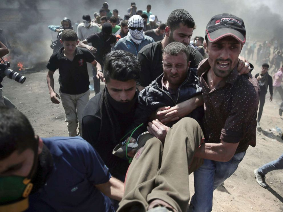 PHOTO: Palestinian protesters carry an injured man who was shot by Israeli troops during a protest at the Gaza Strips border with Israel, May 14, 2018.