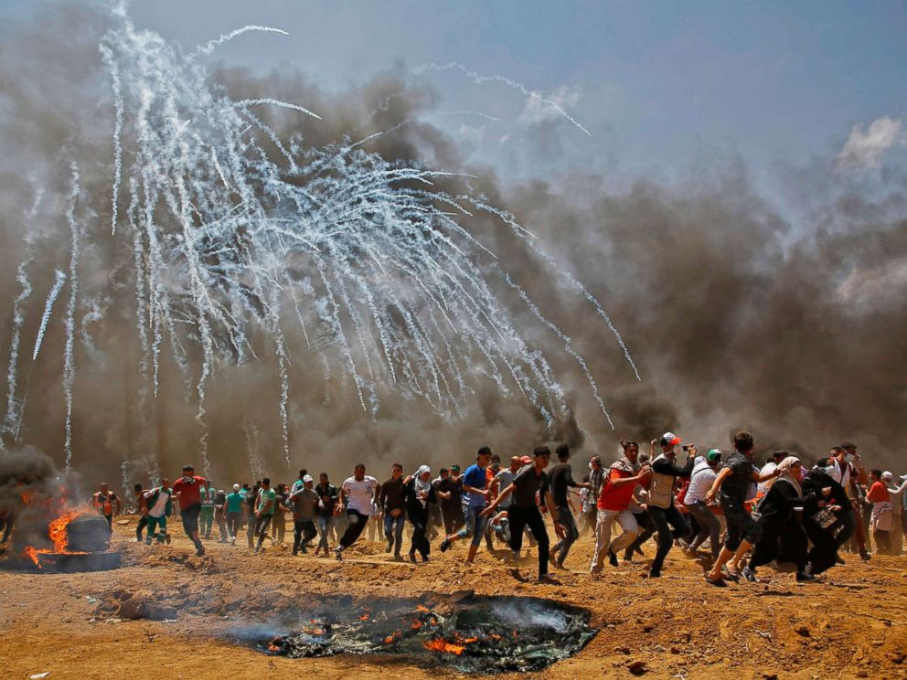 PHOTO: Palestinians run for cover from tear gas during clashes with Israeli security forces near the border between Israel and the Gaza Strip, east of Jabalia, May 14, 2018.