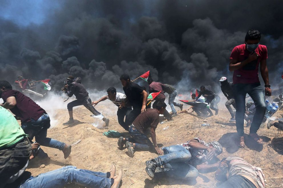 PHOTO: Palestinian demonstrators run for cover from Israeli fire and tear gas during a protest against U.S. embassy move to Jerusalem at the Israel-Gaza border in the southern Gaza Strip May 14, 2018.