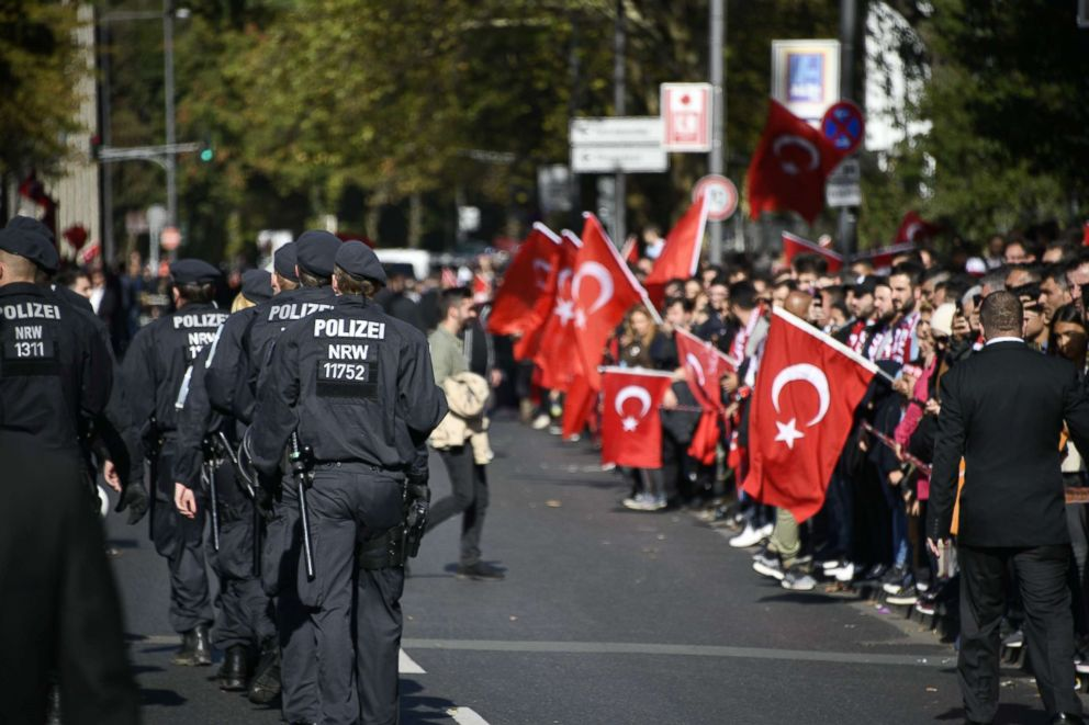 PHOTO: Well wishers hold Turkish flags as police officers walk near to Colognes Central Mosque prior to the visit of the Turkish President, Sept. 29, 2018, in Cologne, Germany.
