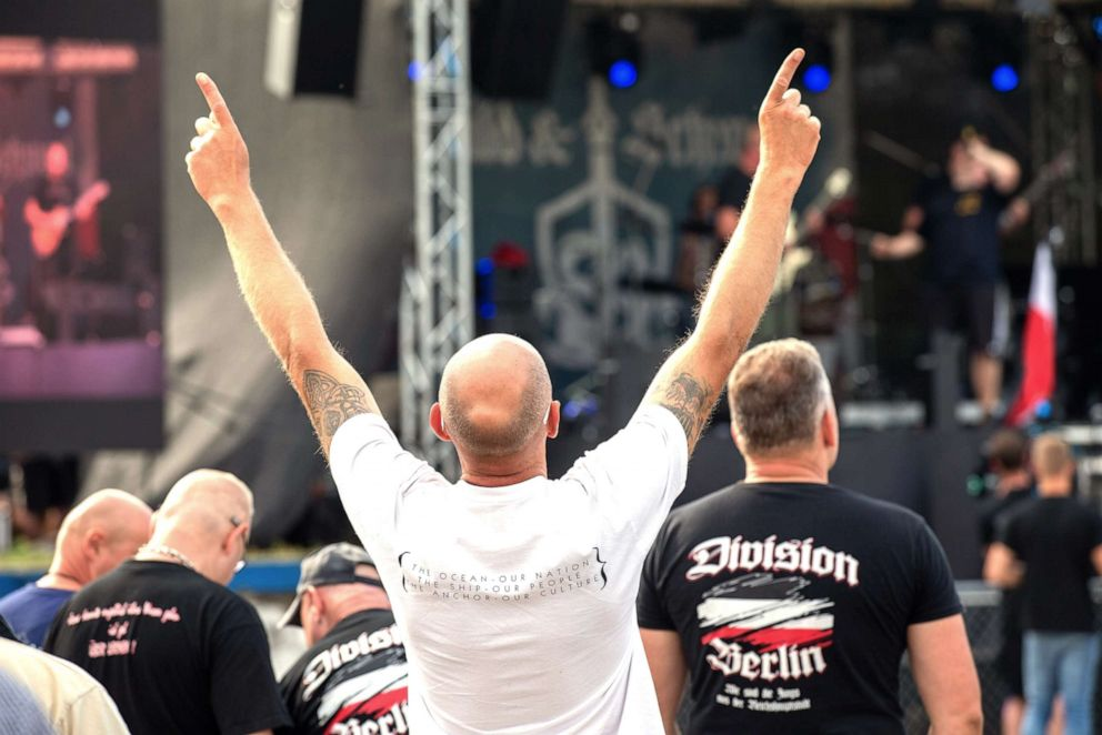 PHOTO: A man moves his arms to the music, which is played on the stage of the right rock festival Shild und Schwert, June 22, 2019.